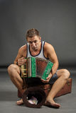 Portrait of a man with accordion sitting on retro suitcase Stock Photography