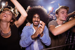 Portrait of man amidst crowd at nightclub. Portrait of young man amidst crowd enjoying at nightclub Stock Image
