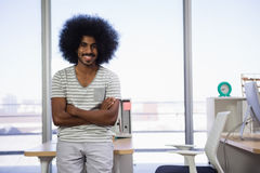 Portrait of man with arms crossed at office. Portrait of smiling young man with arms crossed standing at office Stock Image