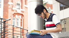 Portrait of man asian student sitting on stairs and reading book stock footage