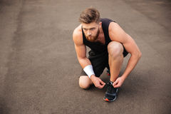 Portrait of man athlete ties his shoelaces Stock Photo