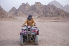 Portrait of a man on an ATV. Quad bikes safari in desert near Sharm El Sheikh, Egypt. Powerful fast off-road four-wheel drive ATVs, motorcycles in sandy desert stock photography