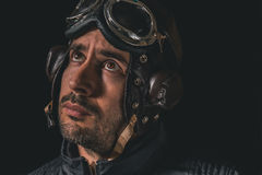 Portrait of a man with aviator helmet and goggles looking away to the distance stock photo