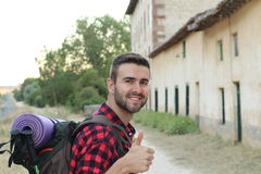 A portrait of a man with backpack giving thumb up isolated on stunning European countryside background with copy space Royalty Free Stock Photo