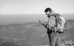 Portrait of man backpacker standing on peak of the mountain Stock Image