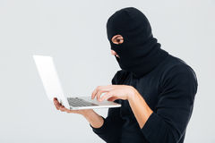 Portrait of man in balaclava standing and using laptop Royalty Free Stock Photography