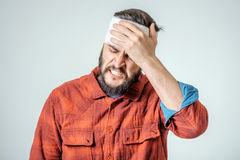 Portrait of man with bandage. S wrapped around his head  on gray background Royalty Free Stock Images