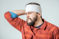 Portrait of man with bandage. S wrapped around his head isolated on gray background Royalty Free Stock Images