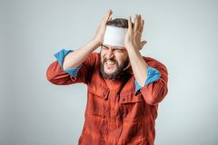 Portrait of man with bandage. S wrapped around his head  on gray background Stock Photos