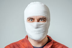 Portrait of man bandaged up. With a head injury isolated on gray Royalty Free Stock Photography