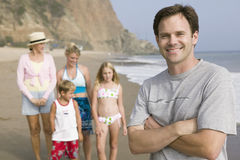 Portrait of man on beach with family stock images