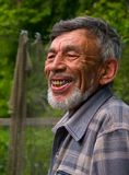 Portrait of Man with Beard 6. A portrait of the old weather-burned smiling man with grey beard. Sunny day, summer. Russian Far East, Primorye Royalty Free Stock Images