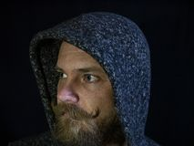 Portrait of a man with a beard and mustache in the hood with a serious face on a black background.  stock photo