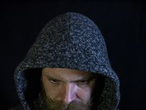 Portrait of a man with a beard and mustache in the hood with a serious face on a black background.  stock photography