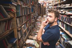 Man with a beard standing on the background of an atmospheric public library and looking at the bookshelf. Portrait of a man with a beard standing on the royalty free stock images