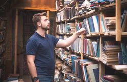 Portrait of a man with a beard who takes books from a library shelf. A student is looking for books in a bible. Self-concept concept royalty free stock photo