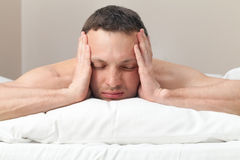 Portrait of man in bed with headache Stock Photo