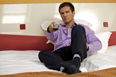 Portrait of man on bed using remote control Stock Photos