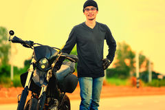 Portrait of man biker standing on road with motorcycle Royalty Free Stock Photography