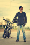 Portrait of man biker standing on road with motorcycle Stock Images