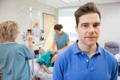 Portrait of Man with Birthing Wife in Background Royalty Free Stock Image