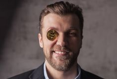 Portrait of man with bitcoin instead of eye Stock Images
