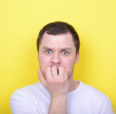 Portrait of man biting nails against yellow background Royalty Free Stock Photography