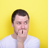 Portrait of man biting nails against yellow background Stock Photography