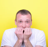 Portrait of man biting nails against yellow background Royalty Free Stock Image