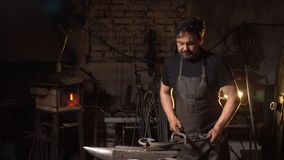 Portrait of a man of a blacksmith in the working atmosphere. Brutal man looks and smiles at the camera. Portrait of a man of a blacksmith in the working Stock Photo