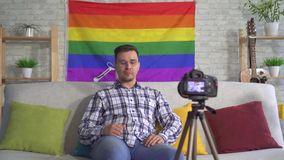 Portrait man blogger middle-aged in the shirt on the background of the flag of the LGBT records video. Portrait man blogger middle-aged in the shirt and glasses stock video footage