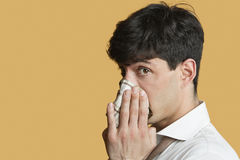 Portrait of a man blowing his nose over colored background Stock Images