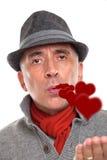 Portrait of a man blowing kisses. Portrait of a man wearing a hat blowing kisses stock image
