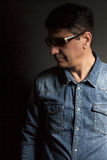 Portrait of man in Blue jean shirt with sunglasses on black back. Ground Royalty Free Stock Photography