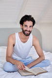 Portrait of man book relaxing bed Royalty Free Stock Image