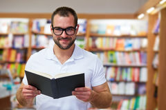 Portrait of a man in a bookstore. Portrait of a man in a polo shirt with a book in a bookstore stock images