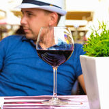 Portrait of a man in a cafe with a glass of red wine. Royalty Free Stock Images