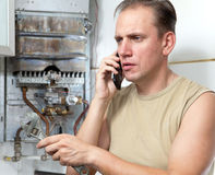 Portrait The man calls by phone to cause the repairman of gas water heaters. The man calls by phone to cause the repairman of gas water heaters Royalty Free Stock Photo