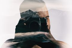 Portrait of a man with a camera. Double exposure, beautiful mountain landscape background. Made in vintage style royalty free stock photo