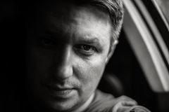 Portrait of a man in a car close-up in black and white tones. Monochrome photo.