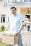 Portrait of man carrying cardboard box while moving house with family in background Stock Images