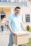 Portrait of man carrying cardboard box while moving house with family in background Royalty Free Stock Image