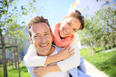 Portrait of man carrying his girlfriend on the back Royalty Free Stock Images