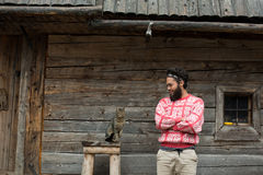 Portrait of man and cat. Portrait of young hipster man with beard and cat in front of wooden house Royalty Free Stock Photo