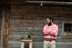 Portrait of man and cat. Portrait of young hipster man with beard and cat in front of wooden house Stock Photos