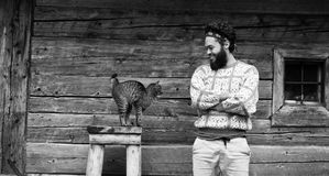 Portrait of man and cat. Portrait of young hipster man with beard and cat in front of wooden house Stock Photo
