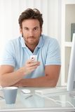 Portrait of man with cellphone handheld. Portrait of smiling man sitting at desk with cellphone handheld, looking at camera Royalty Free Stock Image