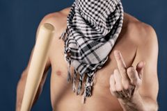 Portrait of a shirtless man in checkered scarf holding a baseball bat and shows finger on blue background royalty free stock photo