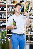 Portrait of  man choosing bottle of wine in shop Stock Images