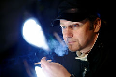 Portrait of the man with a cigarette in the light of headlights. Stock Image